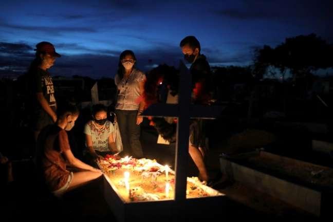 Familiares visitam túmulo de vítima da covid-19 em Manaus (AM)