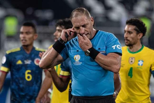 Nestor Pitana conversa com o VAR durante a partida entre Brasil e Colômbia