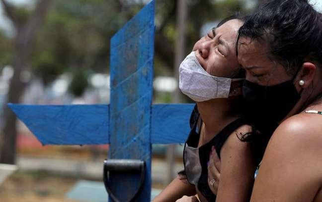 Kelvia Andrea Goncalves chora durante enterro da mãe que morreu de covid-19, em cemitério de Manaus REUTERS/Bruno Kelly