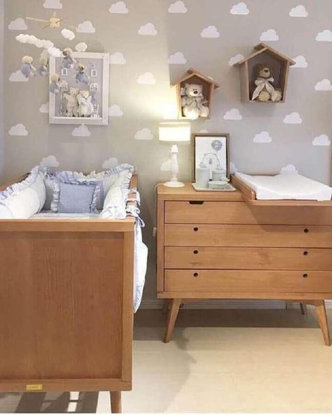5. Cômoda com trocador de madeira para quarto de bebê cinza decorado com papel de parede de nuvens – Foto: Histórias de Casa