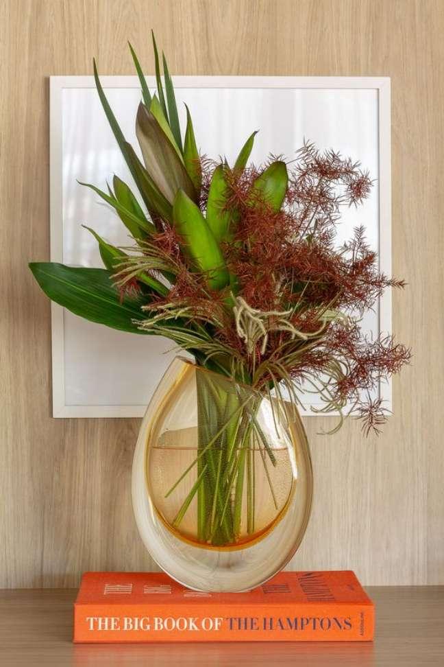 66. Vaso de flor com livro laranja para decorar a estante – Foto Cristais Cadoro