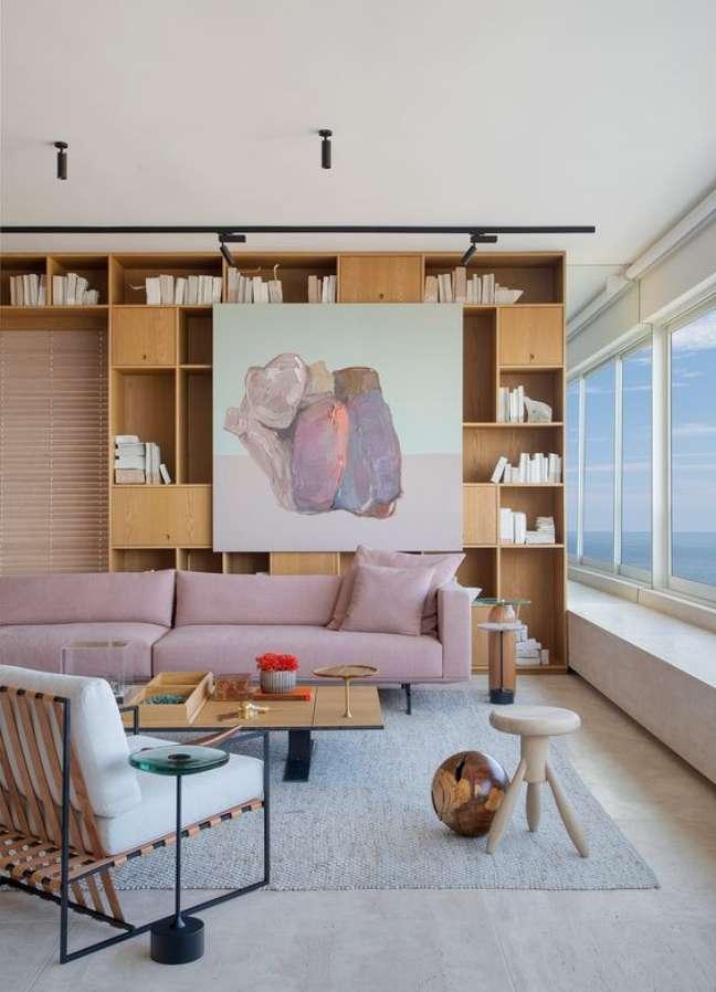 60. Sala com estante de livros e sofá rosa – Foto Casa de Valentina