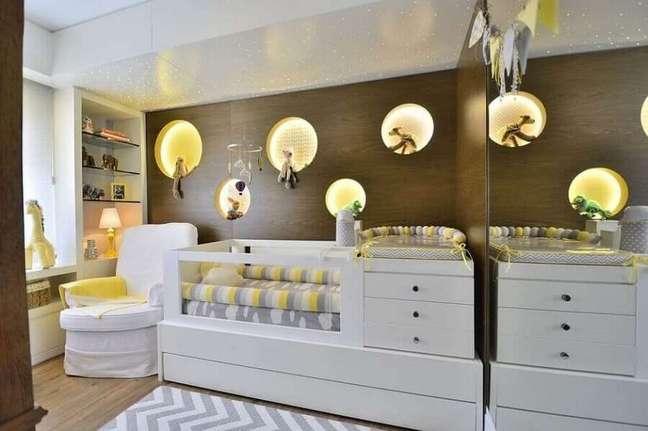 11. Berço com cômoda e trocador para quarto de bebê decorado com painel de madeira com nichos redondos – Foto: BG Arquitetura