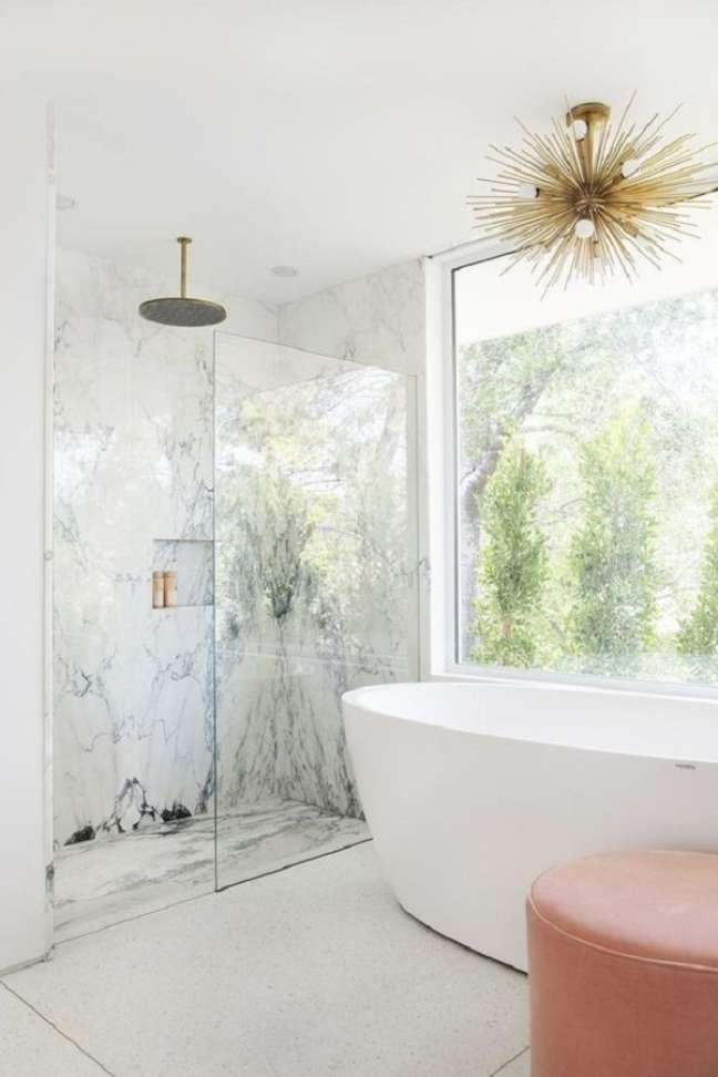 4. Banheiro grande com banheira de imersão decorado com lustre dourado moderno – Foto: Framed & Matted