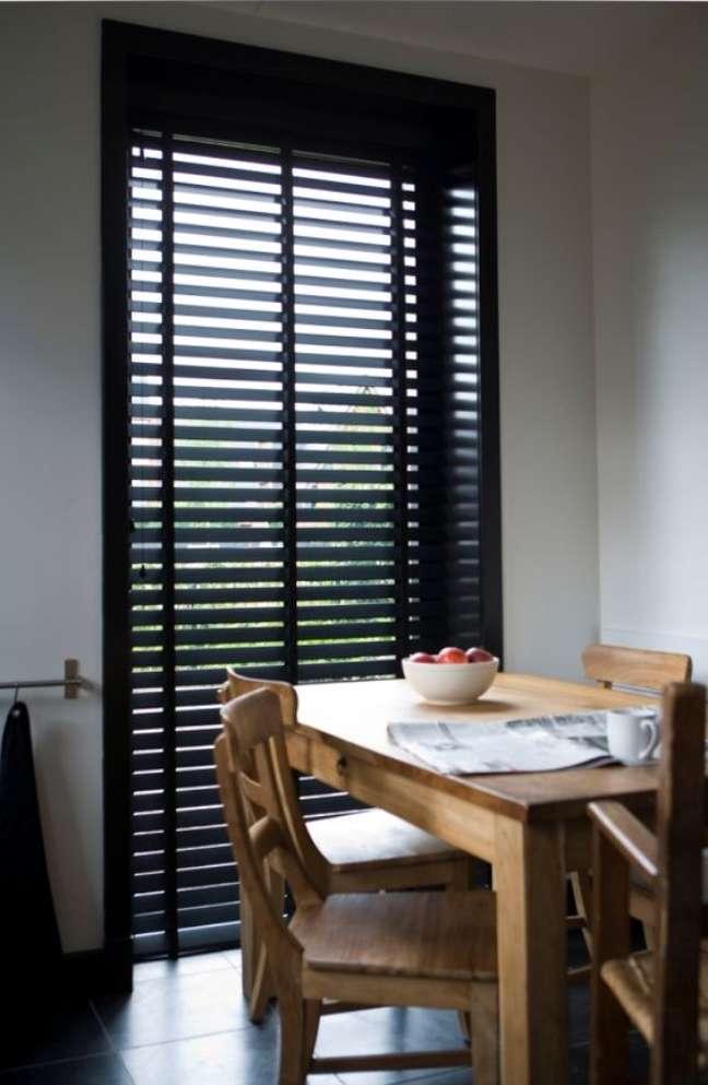15. Sala de jantar com mesa de madeira e persiana preta – Foto Jasnos Hunters