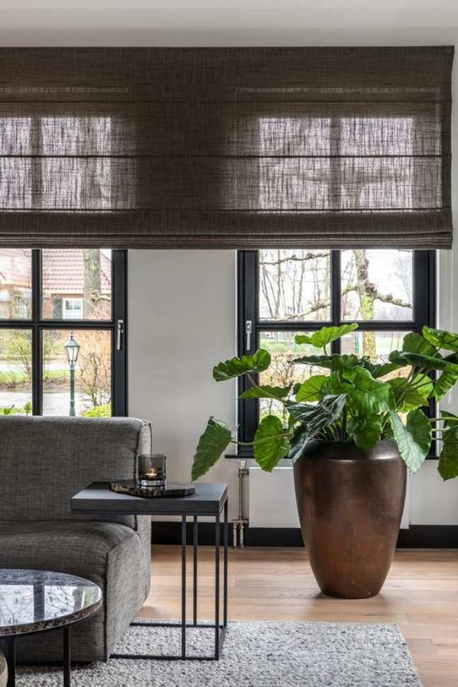8. Sala com persiana preta e vaso de plantas – Foto Hoog Design