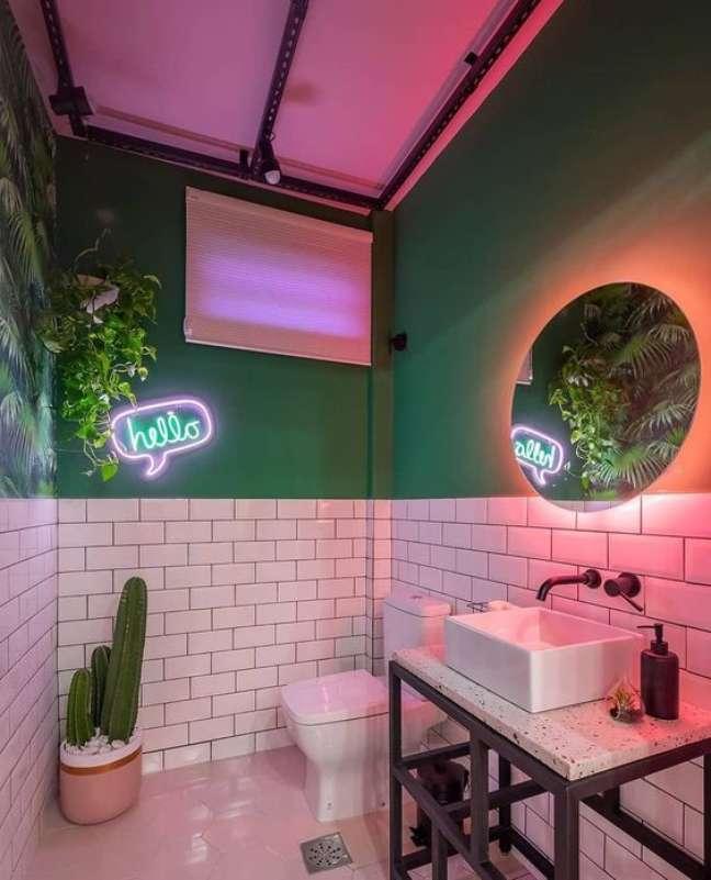52. Banheiro com luz neon cor de rosa e luminaria com frase apontando para o cacto – Foto Liv Decora