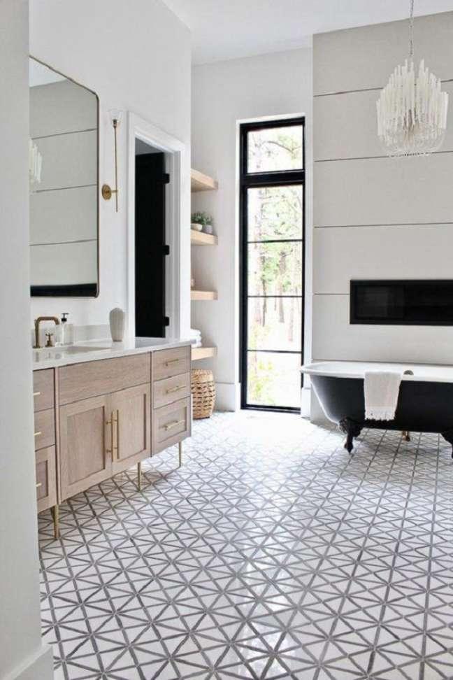 30. Decoração de banheiro grande com banheira preta vitoriana e gabinete de madeira – Foto: Apartment Therapy
