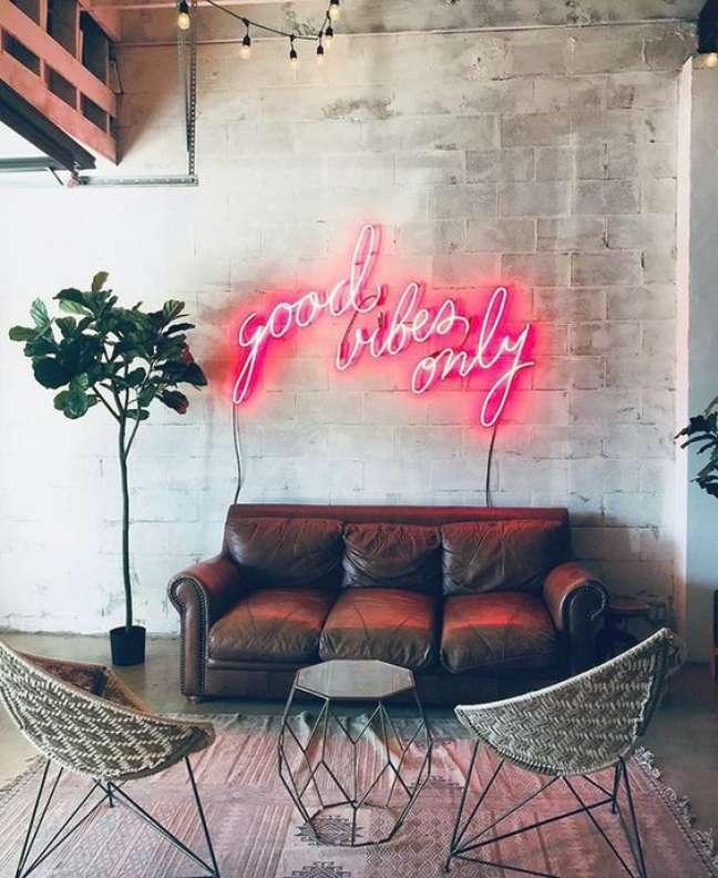 4. Sala estilo industrial com sofá de couro e luz neon – Foto Follow the Colours