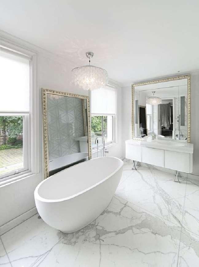 38. Decoração de luxo para banheiro com espelho grande e lustre redondo – Foto: The Architect's Diary