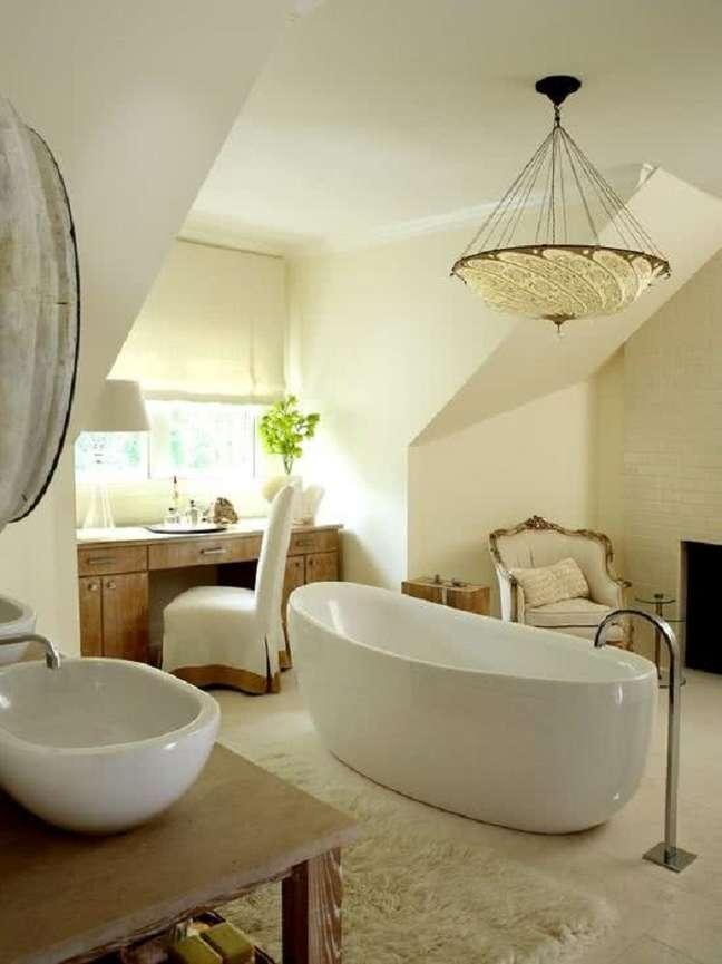 39. Decoração em cores claras com lustre redondo para banheiro grande com banheira – Foto: Pinterest