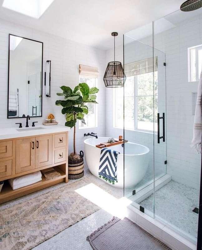 31. O gabinete de madeira traz um charme especial para a decoração do banheiro grande com banheira – Foto: Jeito de Casa