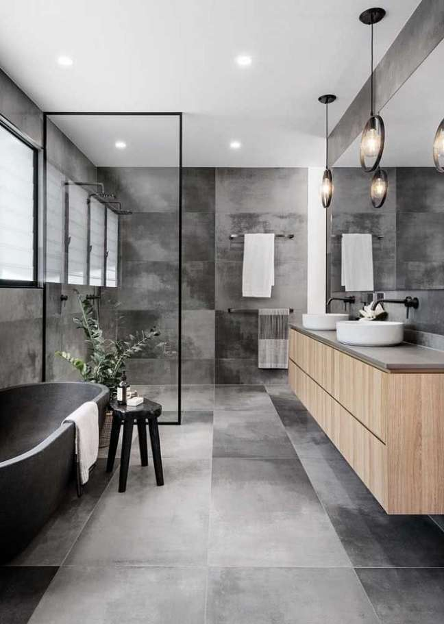 61. Tons de cinza para banheiro grande moderno decorado com gabinete de madeira – Foto: Elle Decor