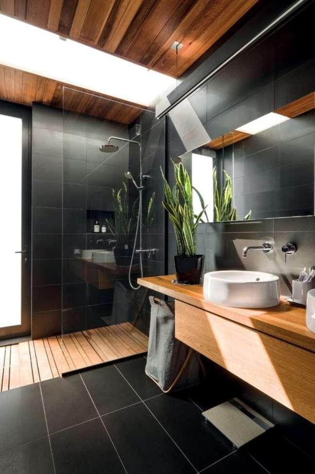 8. Os detalhes em madeira ajudam a deixar o banheiro grande moderno e preto mais aconchegante – Foto: Futurist Architecture
