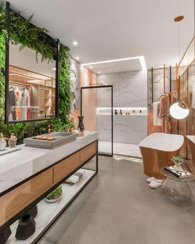 36. Decoração de banheiro grande moderno com jardim vertical e detalhes na cor cobre – Foto: Pinterest