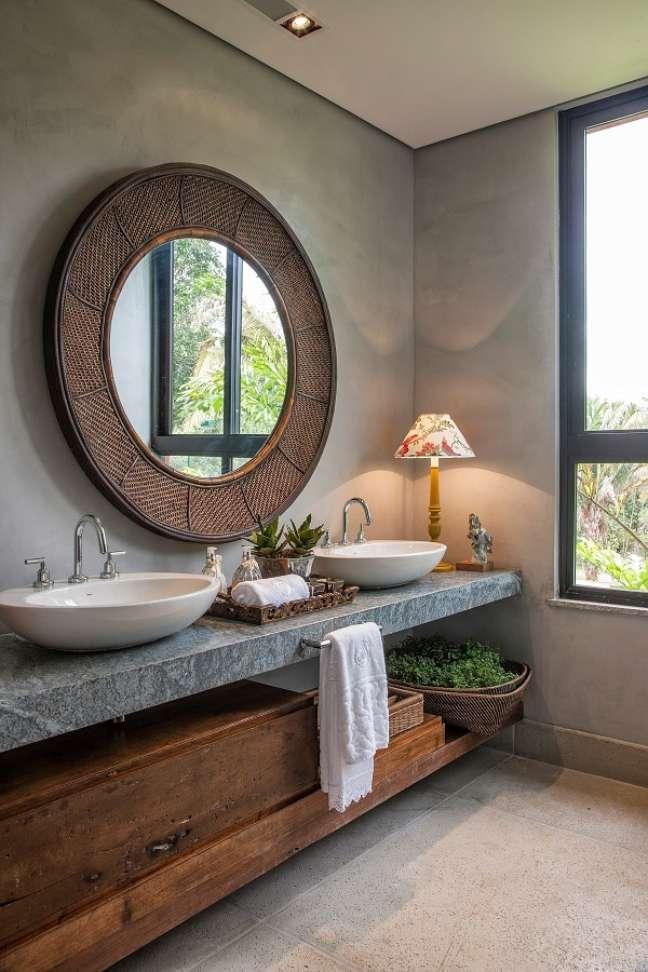 16. Banheiro grande decorado com parede de cimento queimado e espelho redondo rústico – Foto: Pinterest