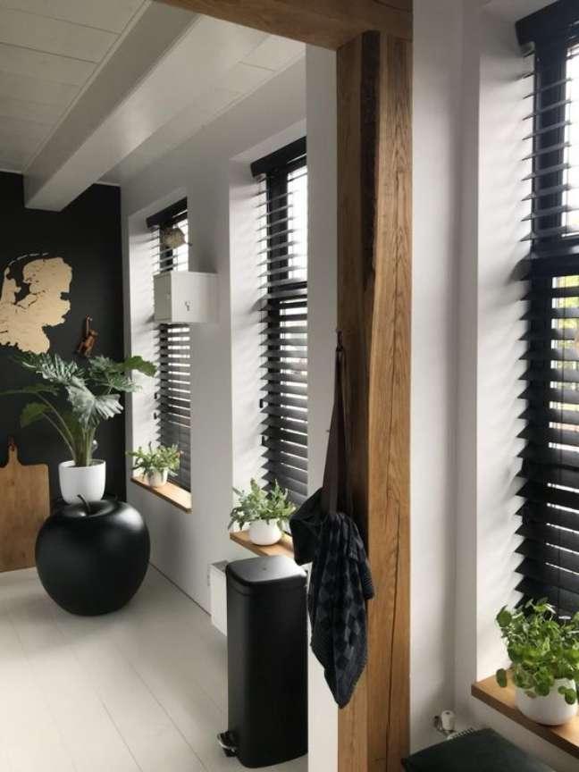 2. Casa com persiana preta horizontal e vasos de plantas decorando o corredor – Foto Studio Zinning