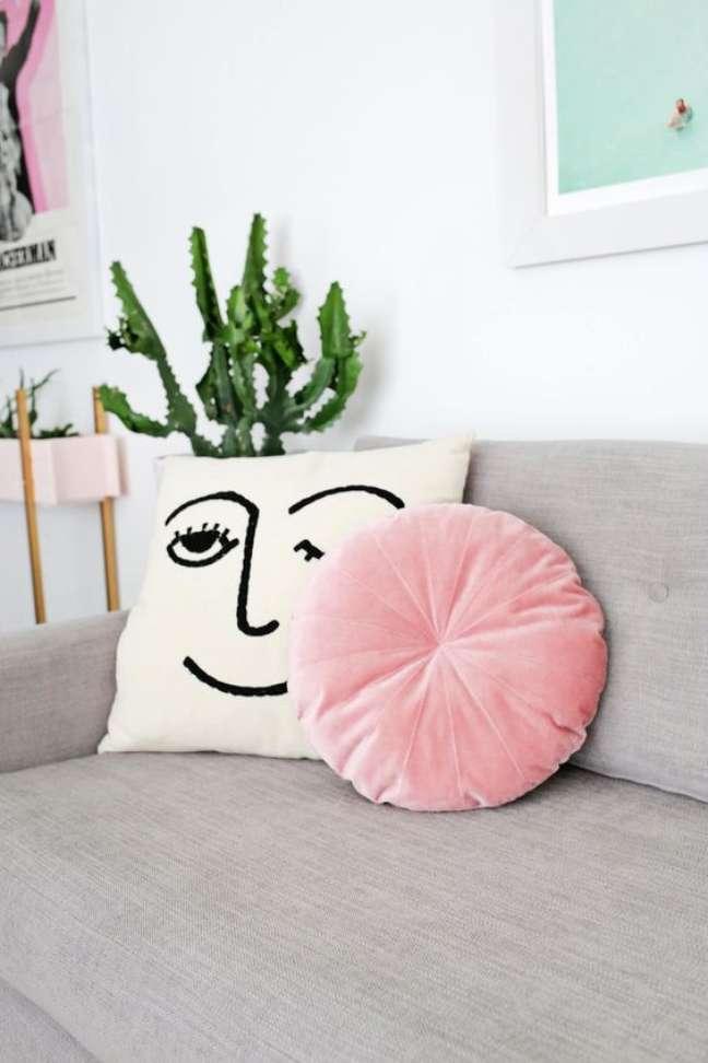 27. Almofada redonda rosa no sofá cinza – Foto Livingly