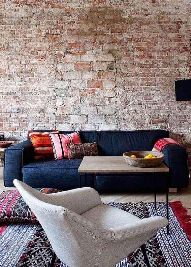 35. Sala com parede de tijolinho rustico e sofá azul marinho – Foto Blue Door Living