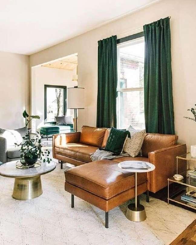 42. Sala de estar decorada com sofá de couro com chaise e cortina na cor verde escuro – Foto Estofos PT