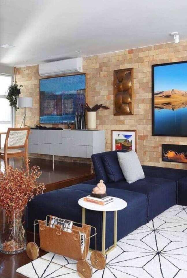 46. Sala moderna com sofá azul marinho e parede de tijolinho – Foto Ideias Decor