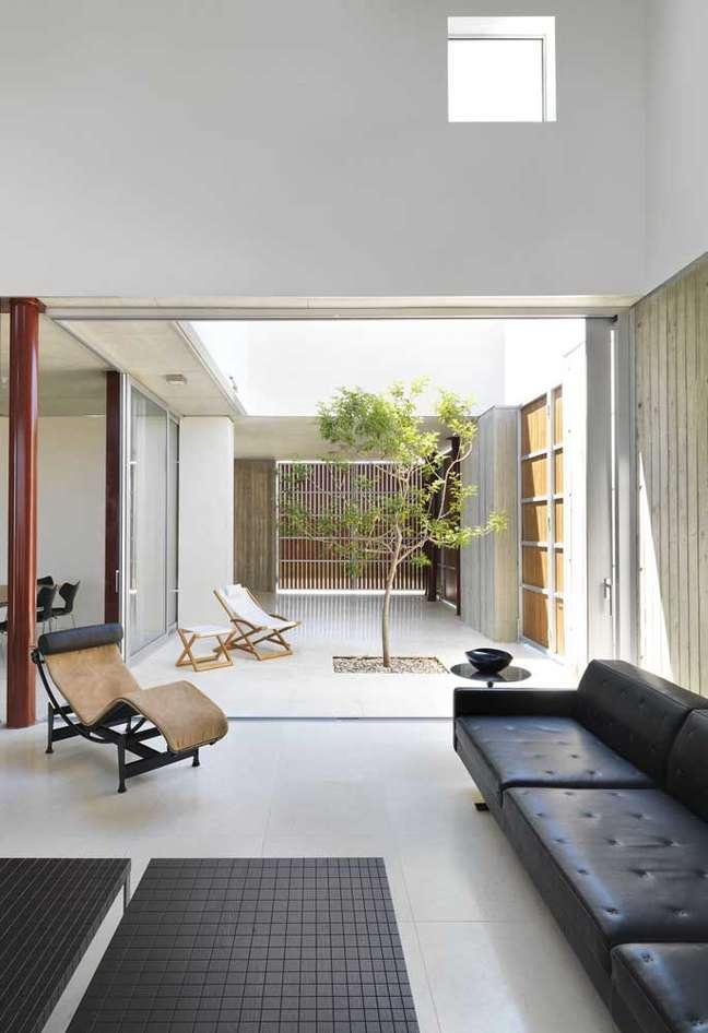 23. Sala com sofá estilo industrial de couro preto e jardim de inverno ao lado para iluminar o ambiente – Foto Pinterest