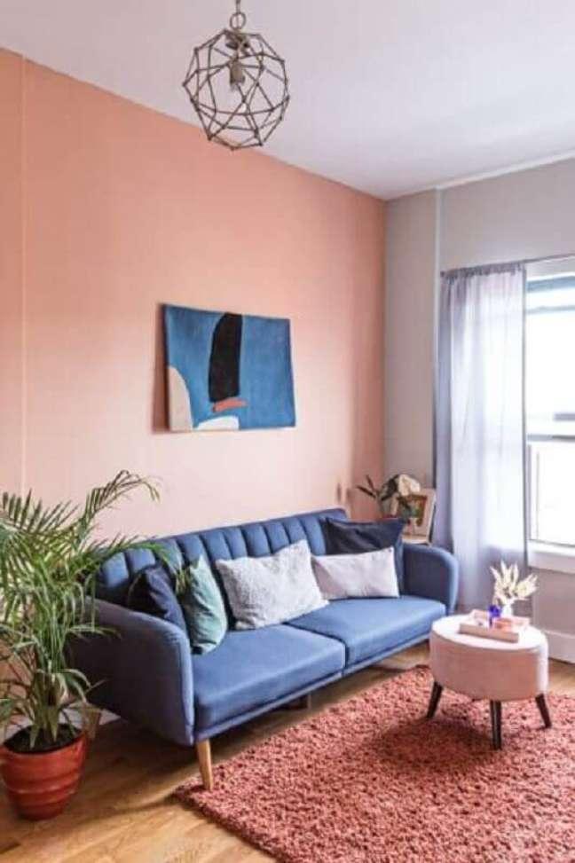 32. Decoração rosa chá para sala de estar com sofá azul – Foto: Domino
