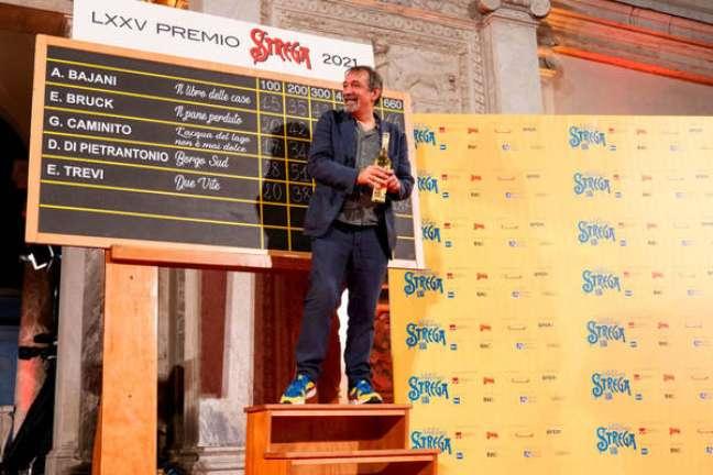 Emanuele Trevi posa em frente à tabela do Prêmio Strega 2021