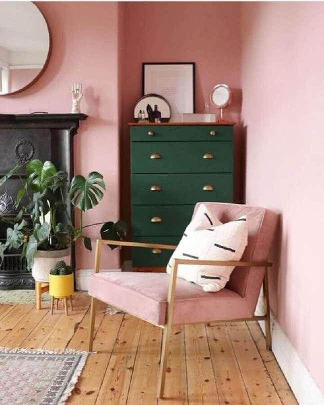 33. Decoração rosa chá para sala decorada com espelho redondo e cômoda verde escura – Foto: Pinterest