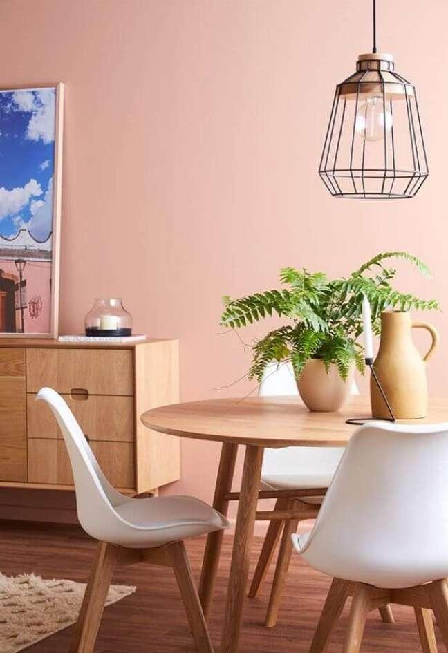 56. Sala de jantar decorada com mesa redonda de madeira e parede rosa chá – Foto: Pinterest