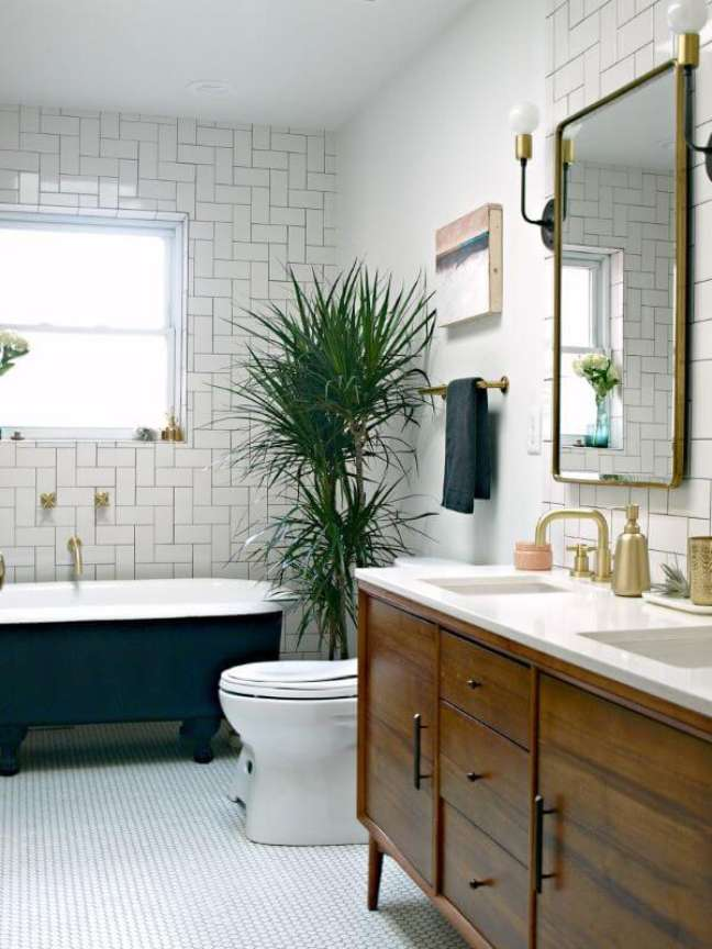 6. Banheiro moderno com banheira de pé e gabinete de madeira – Foto This Little Miggy