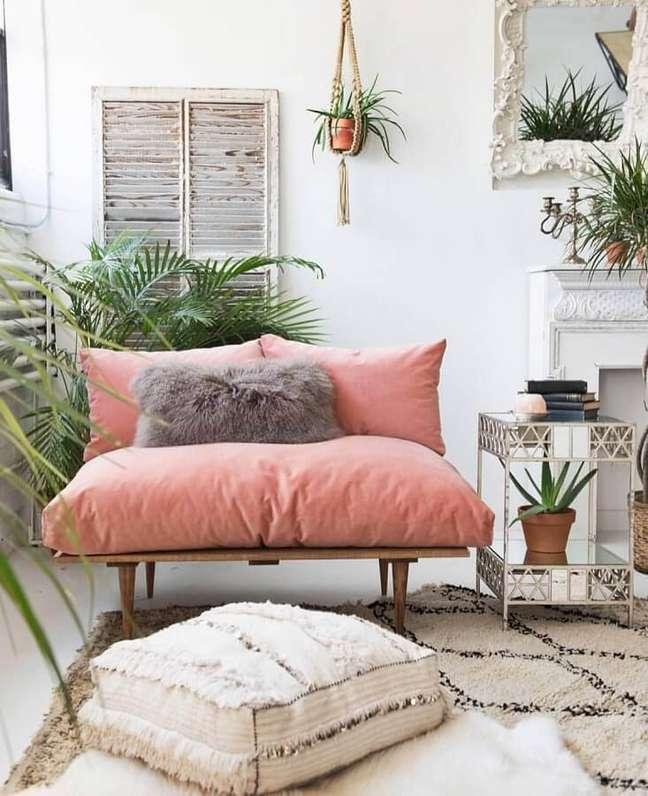 34. Decoração simples com sofá rosa chá de madeira e vasos de plantas – Foto: Pinterest