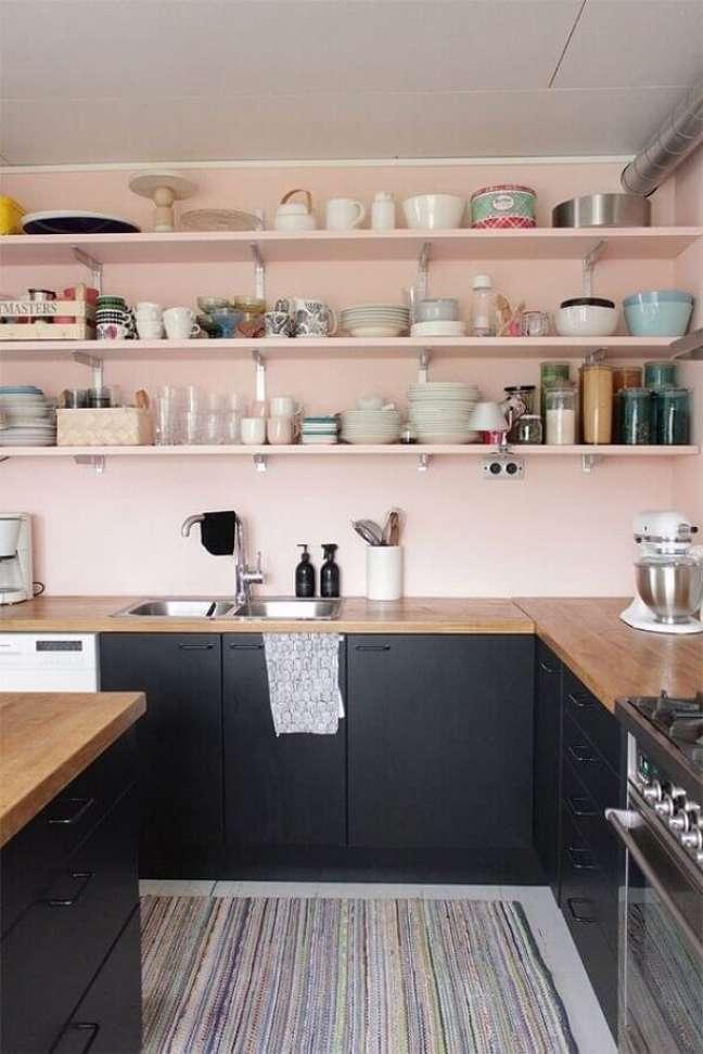 40. Parede rosa chá para cozinha decorada com gabinete preto e bancada de madeira – Foto: Architecture Art Designs