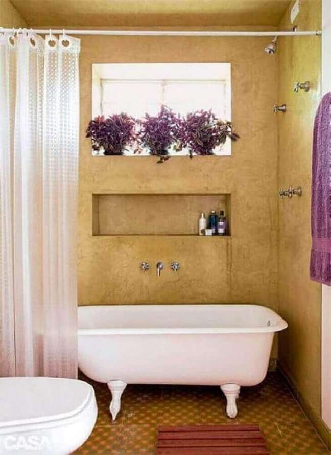 45. Banheira de pé branca na decoração amarela e roxa – Foto Terra
