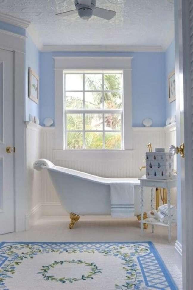 43. Banheira de pé branca com dourado no banheiro decorado em azul – Foto Bornin May
