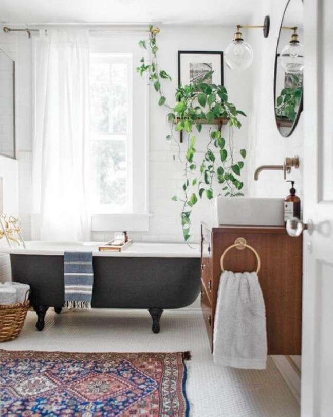 11. Banheira de pé cinza chumbo no banheiro moderno decorado com plantas e gabinete de madeira – Foto Domkapa