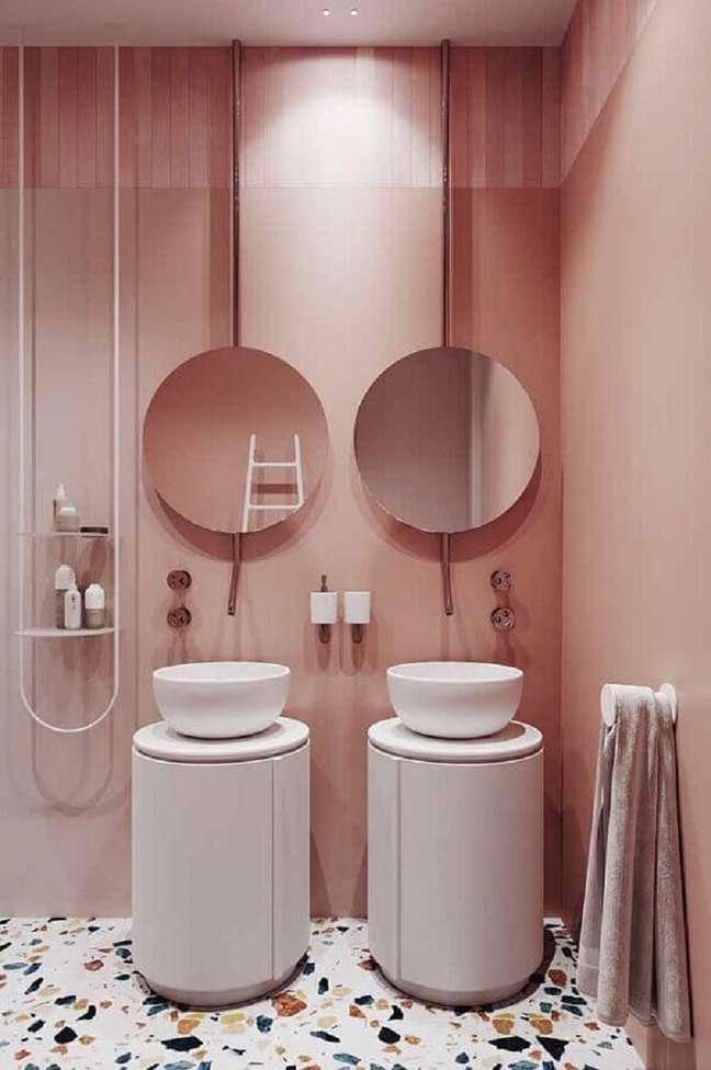 7. Banheiro moderno decorado com espelho redondo e parede rosa chá – Foto: Pinterest