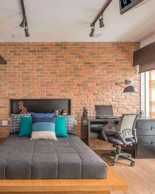 54. Quarto com escritório decorado com parede de tijolinho e escrivaninha preta – Foto: Gigi & Silva Sued