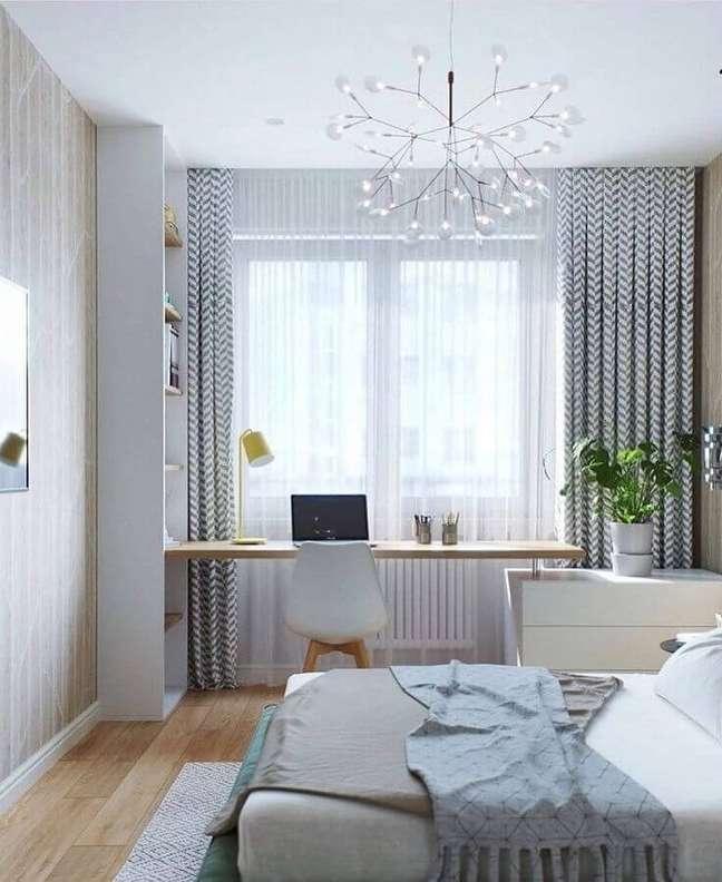 13. Bancada de madeira para quarto com escritório decorado com lustre moderno – Foto: Pinterest