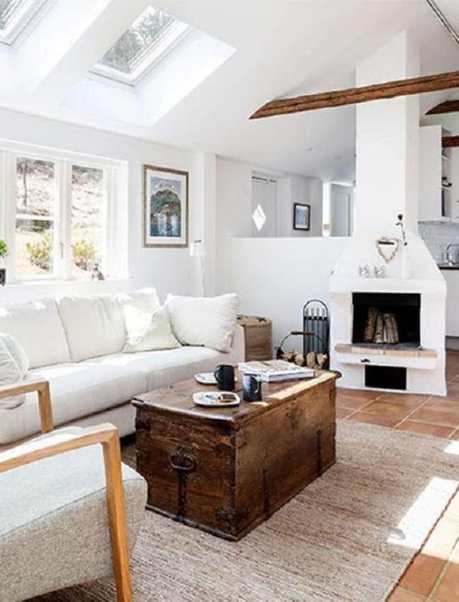 40. Sala com lareira e baú de madeira e tapete bege – Foto Pure Wow
