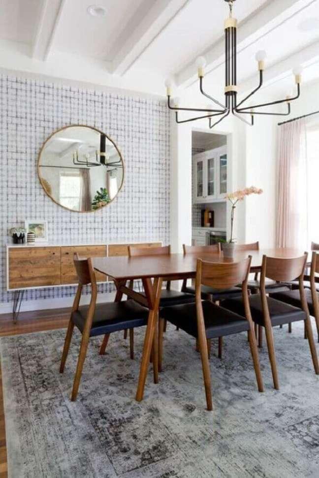 23. Buffet de madeira para sala de jantar decorada com tapete cinza e espelho redondo – Foto: Jeito de Casa