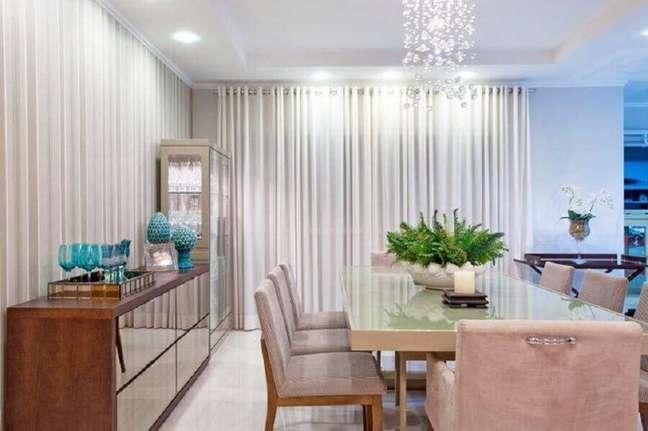 40. Decoração sofisticada para sala de jantar com lustre de cristal e buffet de madeira com porta espelhadas – Foto: Pinterest