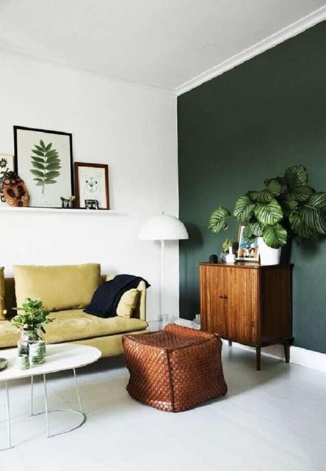 2. Decoração de sala de estar com parede verde e armário de madeira pequeno – Foto: Homedit