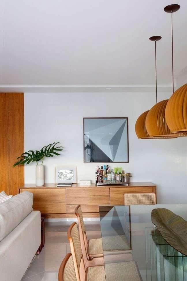 20. Buffet de madeira para sala de jantar decorada com mesa de vidro e luminária redonda de madeira – Foto: Casa de Valentina