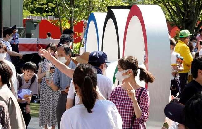 Pessoas posam ao lado dos anéis olímpicos, em frente ao Estádio Olímpico, o principal estádio dos Jogos Olímpicos e Paralímpicos de Tóquio 2020, no Japão 23/07/2021 REUTERS/Fabrizio Bensch