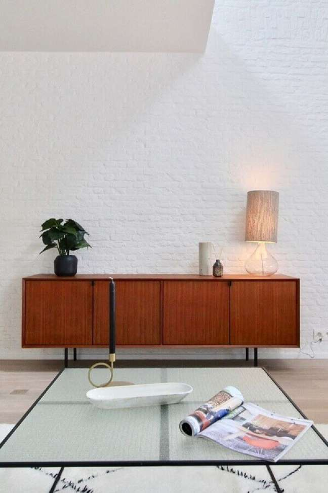 24. Buffet de madeira para sala minimalista decorada com parede de tijolinho branco – Foto: Apartment Therapy