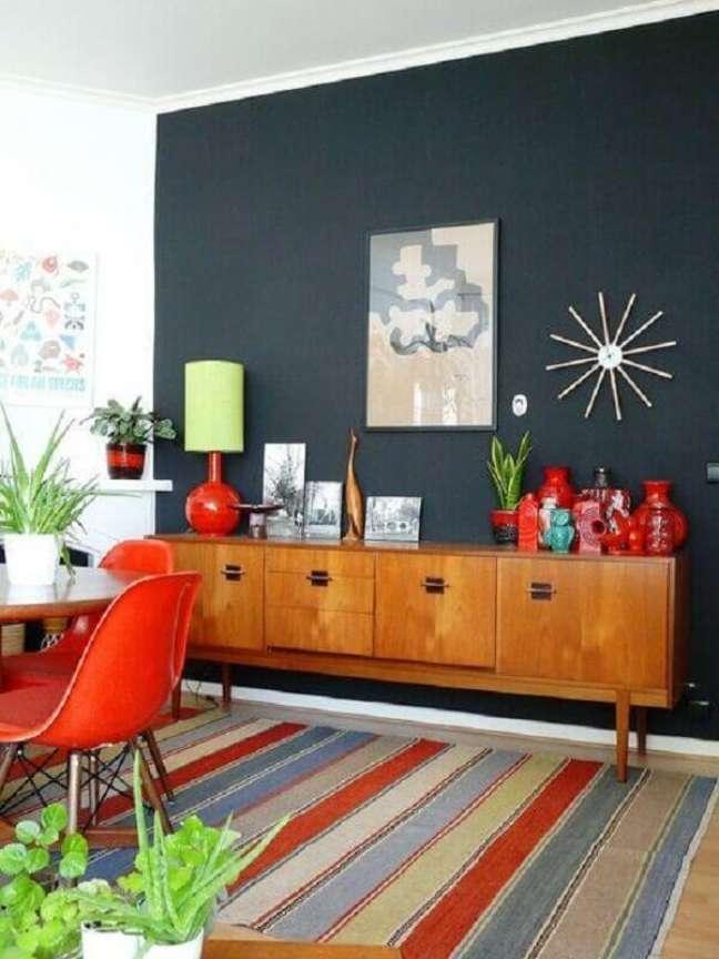 22. Buffet de madeira para sala de jantar decorada com parede preta e tapete listrado colorido – Foto: Pinterest