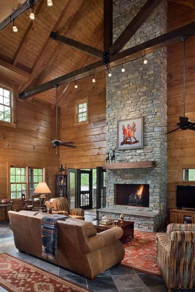 42. Sala rustica de casa do campo com lareira em frente ao sofá – Foto Honestabe