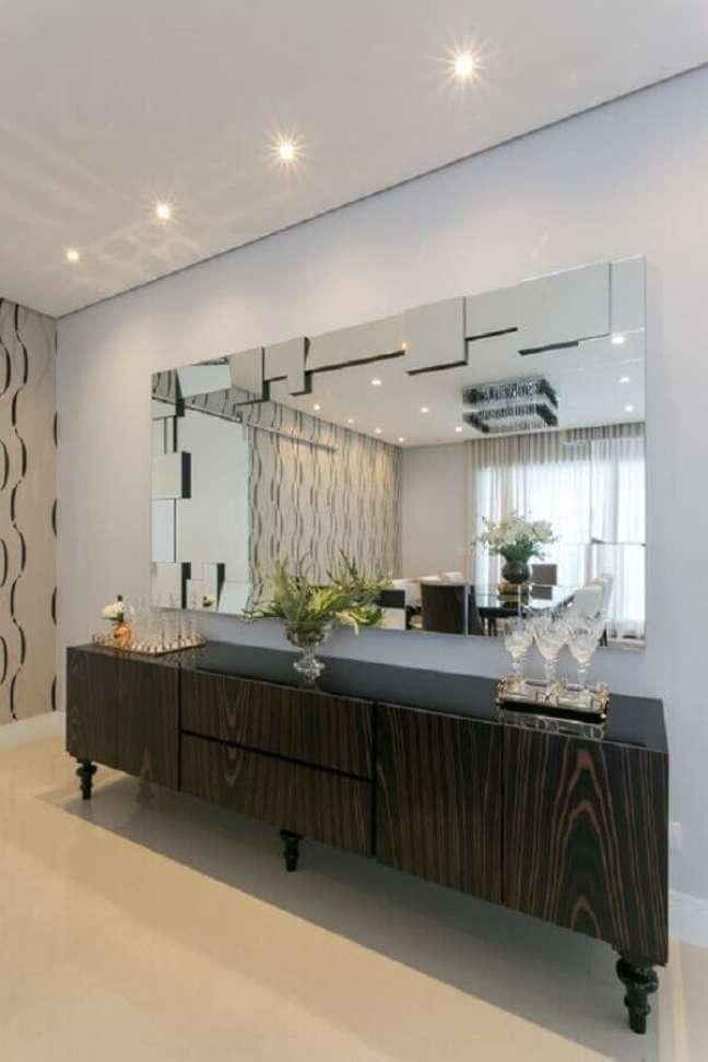 33. Decoração de sala de jantar com espelho grande e buffet de madeira escura – Foto: Art Ville Móveis