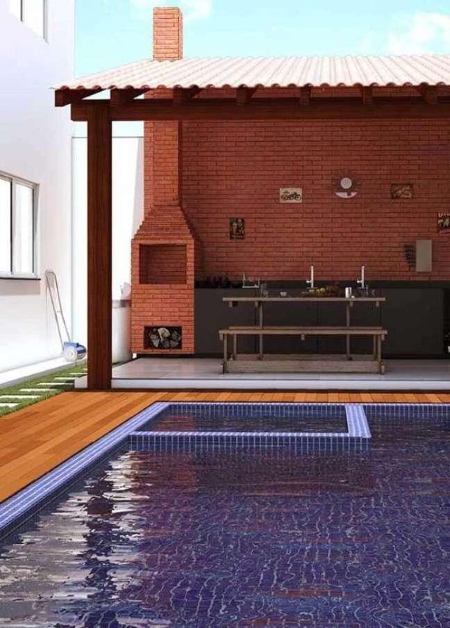 3. Área da piscina com chaminé de Churrasqueira de tijolinho pequena acima da cobertura – Foto Pinterest